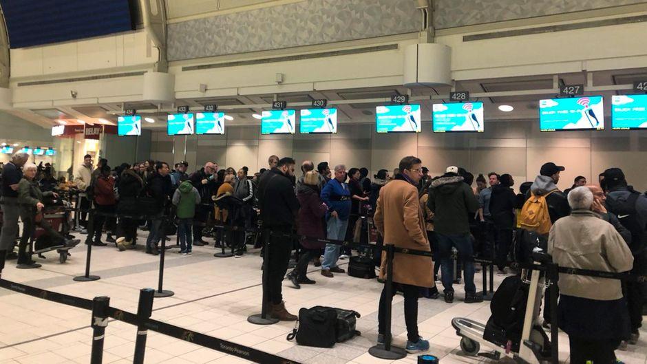 Passagiere warten an den Schaltern am Flughafen.