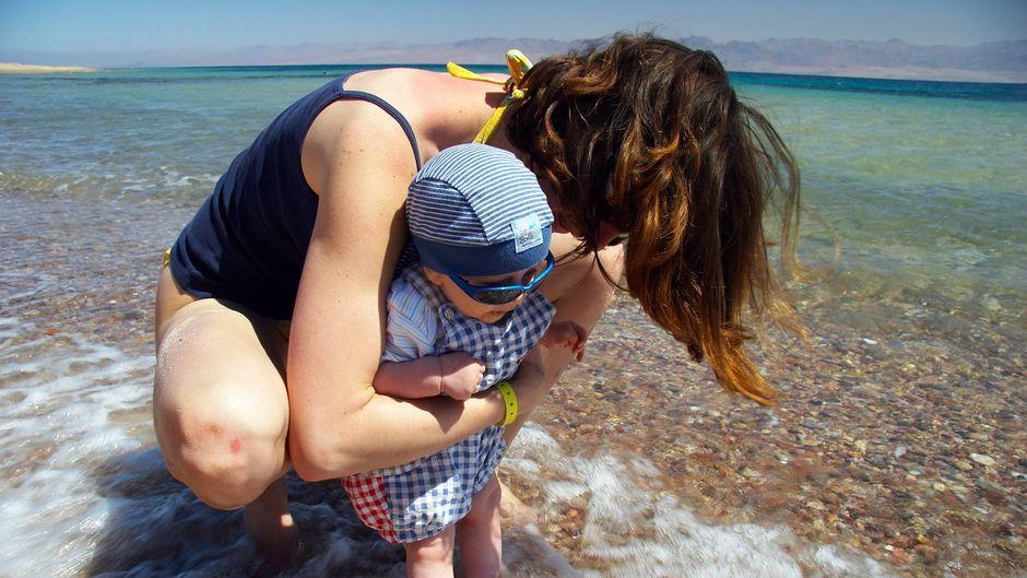 Eine Mutter setzt ihr Baby ins seichte Wasser in Ägypten