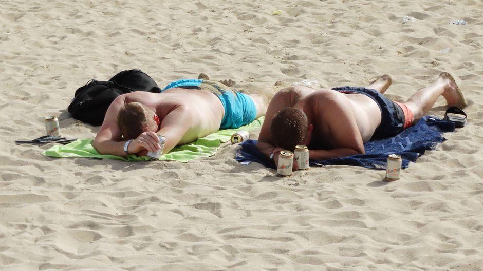 Zwei Männer liegen mit Bierdosen am Strand von Palma de Mallorca.