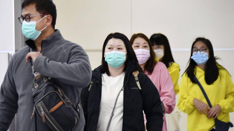 Fluggäste mit Atemschutzmasken.