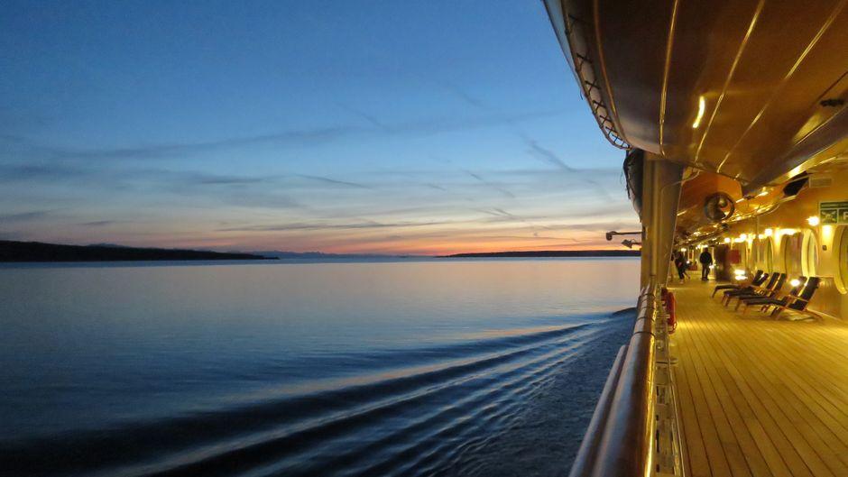 Beleuchtetes Deck auf einem Kreuzfahrtschiff bei Sonnenuntergang.