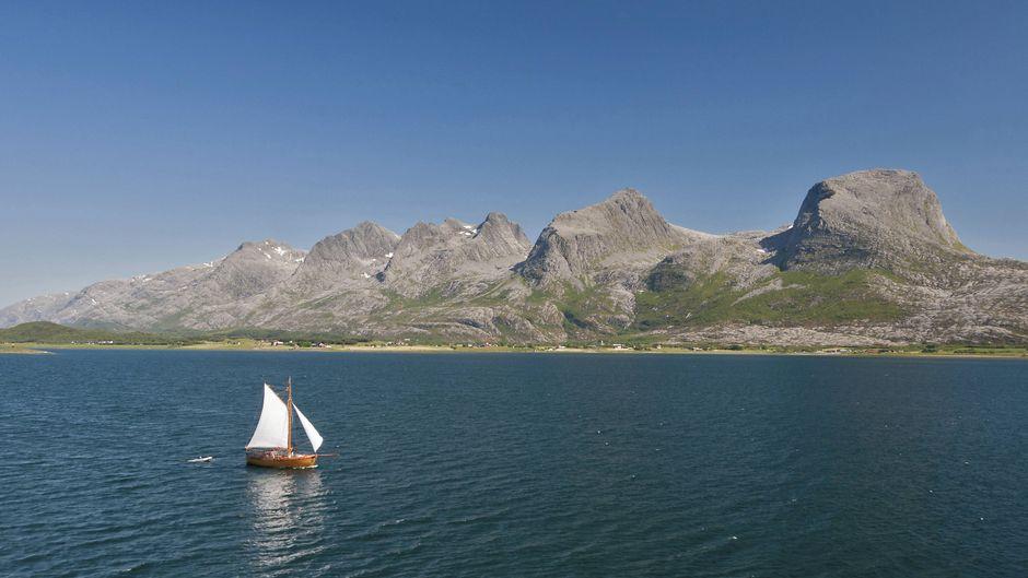Segelschiff vor der Gebirgskette Sieben Schwestern in Norwegen.