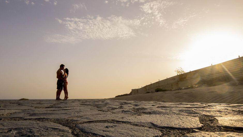 Ein Paar küsst sich im Sonnenuntergang.