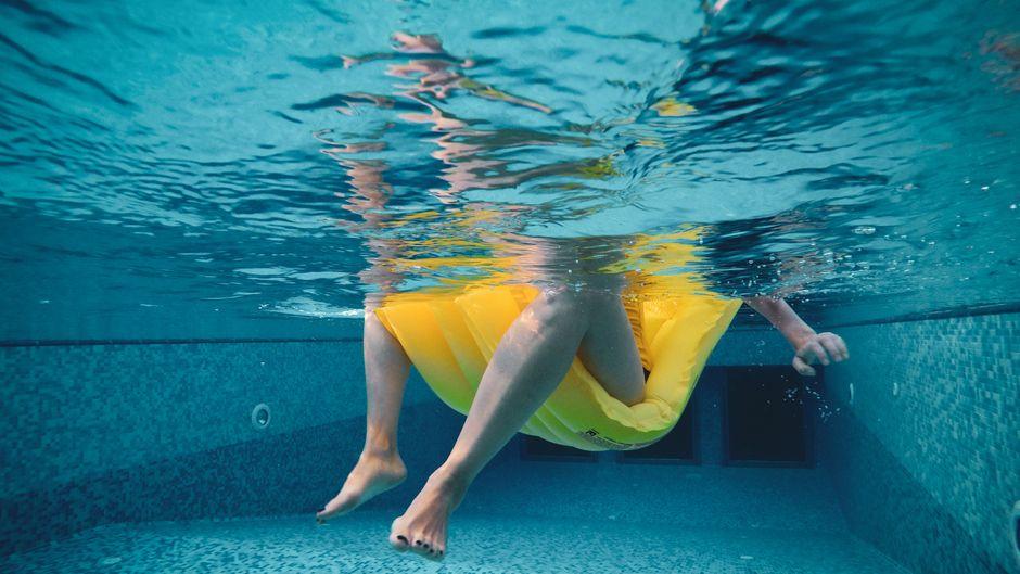 Person auf Luftmatratze im Pool.