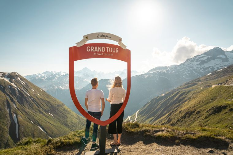 Junges Paar geniesst den Ausblick auf der Grand Tour of Switzerland beim Foto Spot des Furkapasses