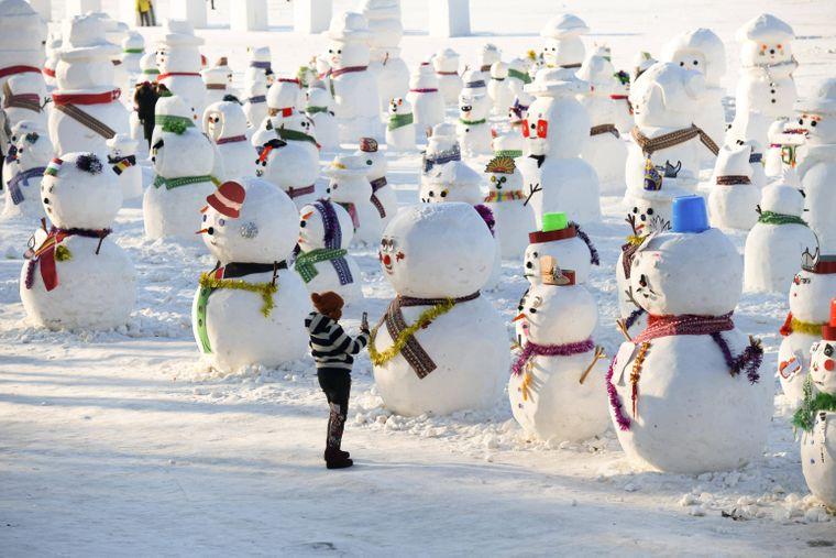 Eine Frau fotografiert Dutzende Schneemänner in Harbin, China.
