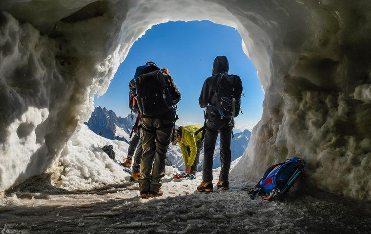 Zwei Guides stehen am Eingang einer Höhle am Mont-Blanc in der Schweiz.