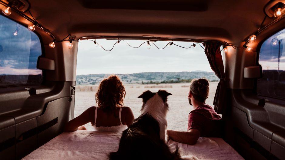Ein Paar im Van blickt in die Landschaft. Für Reisen in Corona-Zeiten müssen alle flexibel sein.