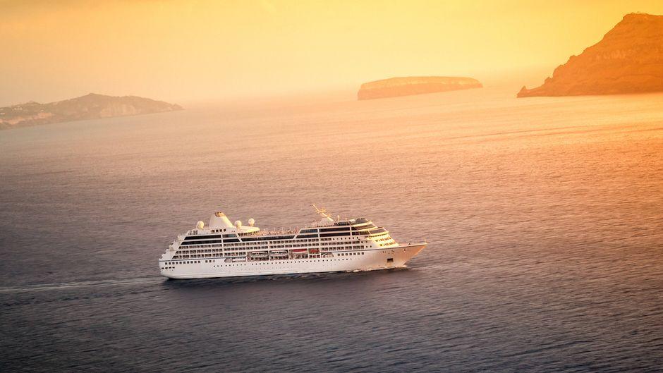 Kreuzfahrtschiff auf dem Meer bei Sonnenuntergang – wann können Urlauber diesen Blick wieder genießen?