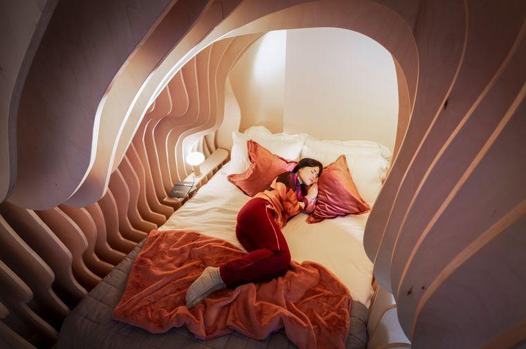 Eine Frau liegt in einem Bett mit hölzernen Wänden und Dach, die an eine Gebärmutter erinnern.