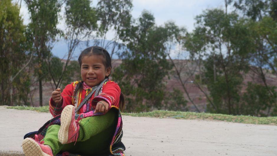 Ein Anden-Mädchen sitzt in Peru an der Straße