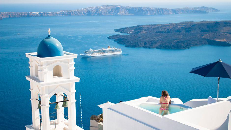 Eine Frau entspannt auf Santorin im Pool – von uns gibt es alle Tipps für den Urlaub in Griechenland.