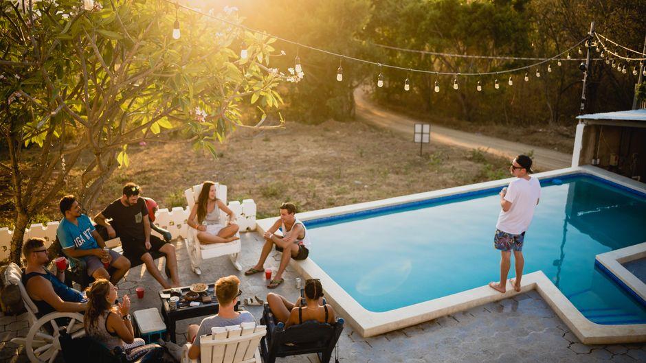 Clique entspannt beim gemeinsamen Urlaub am Pool.