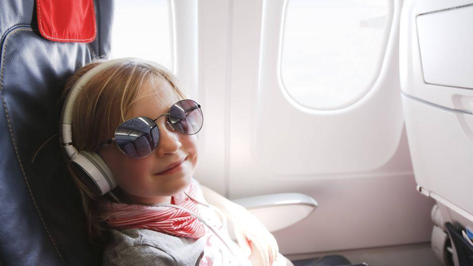 Ein Mädchen fühlt sich sichtlich wohl im Flugzeug.