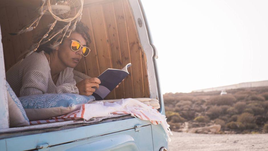 Frau liest Buch im Campervan.