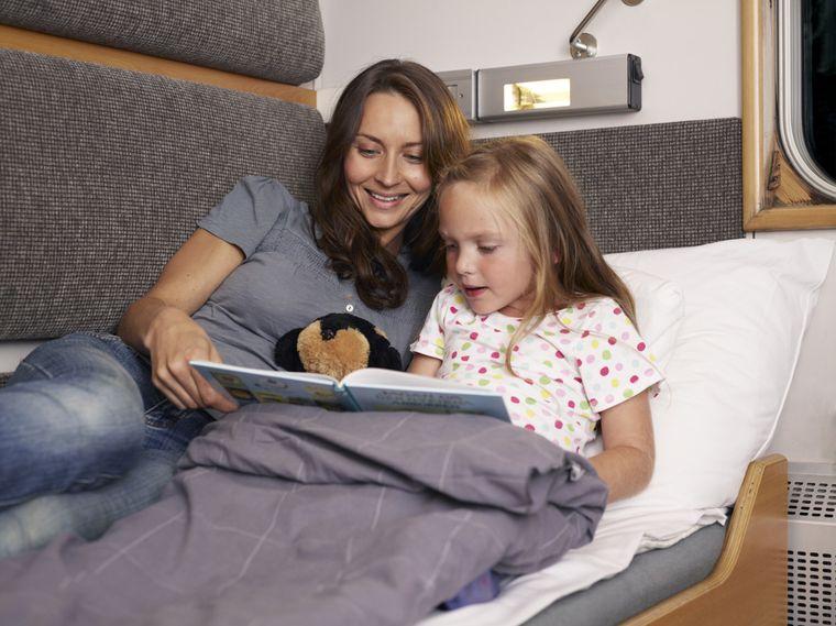 Mutter und Tochter liegen auf einem Bett im Nachtzug in Schweden.