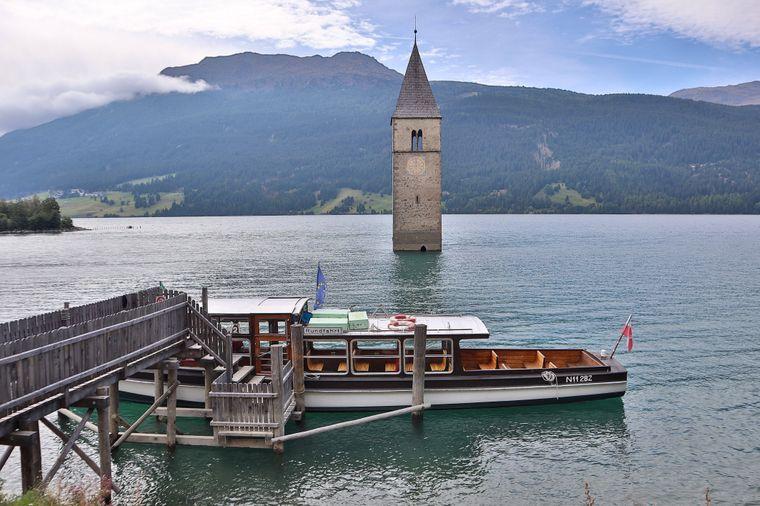 Der Reschensee im Vinschgau mit der alten Kirche von Graun, die im Stausee versunken ist.