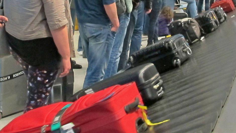 Fluggäste am Kofferband
