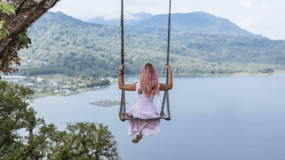 Eine Frau schaukelt mit Aussicht auf Bali, Indonesien.
