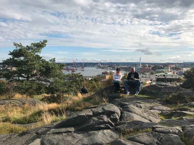 Ein Paar sitzt auf den Felsen vor der Masthuggskyrka und genießt den Blick über Göteborg und den Hafen.