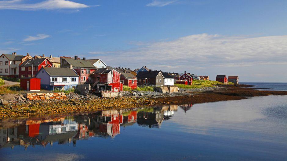 Fischerhäuser auf der Varanger-Halbinsel in Norwegen spiegeln sich im Meer.