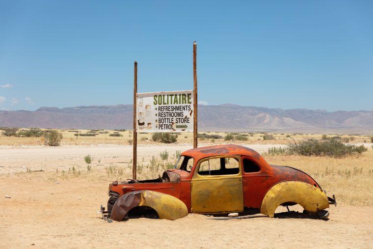 Ein kaputtes Auto steht in Solitaire in Namibia in der Wüste.