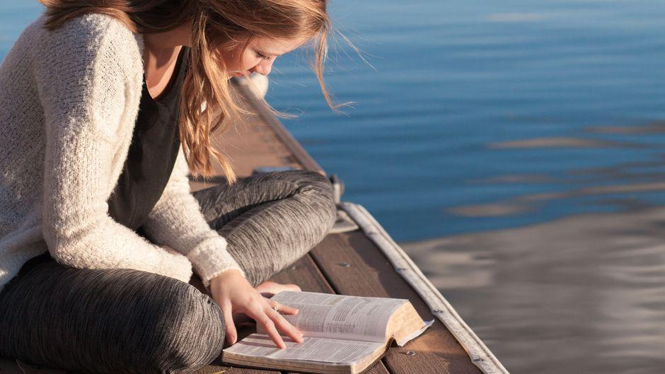 Eine junge Frau liest auf einem Steg am See.