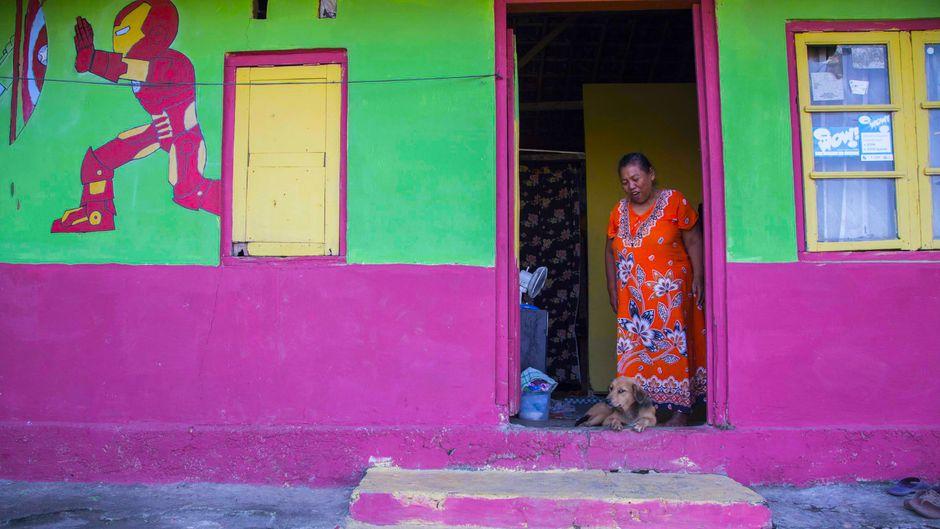 Eine Frau steht an ihrer Haustür.