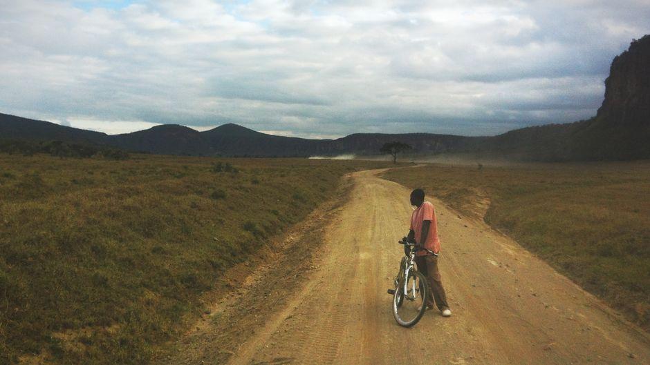 Ein Mann steht mit seinem Fahrrad im Hell's Gate Nationalpark in Kenia.