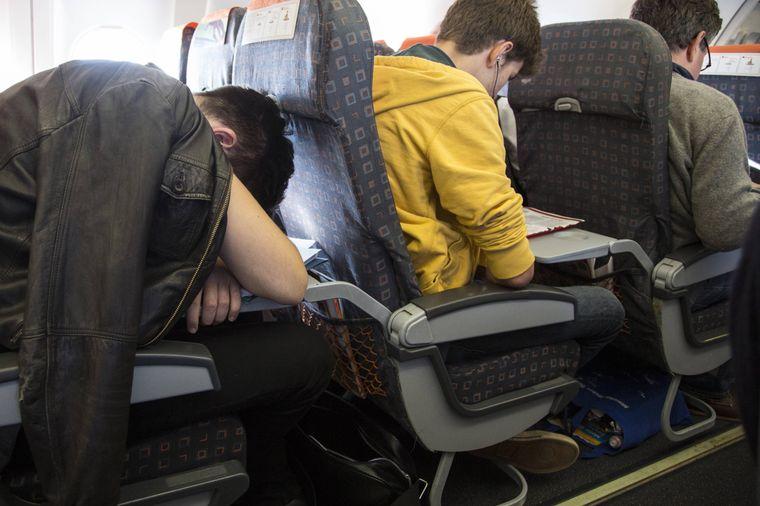 Mann benutzt den Klapptisch im Flugzeug als Kopfstütze.