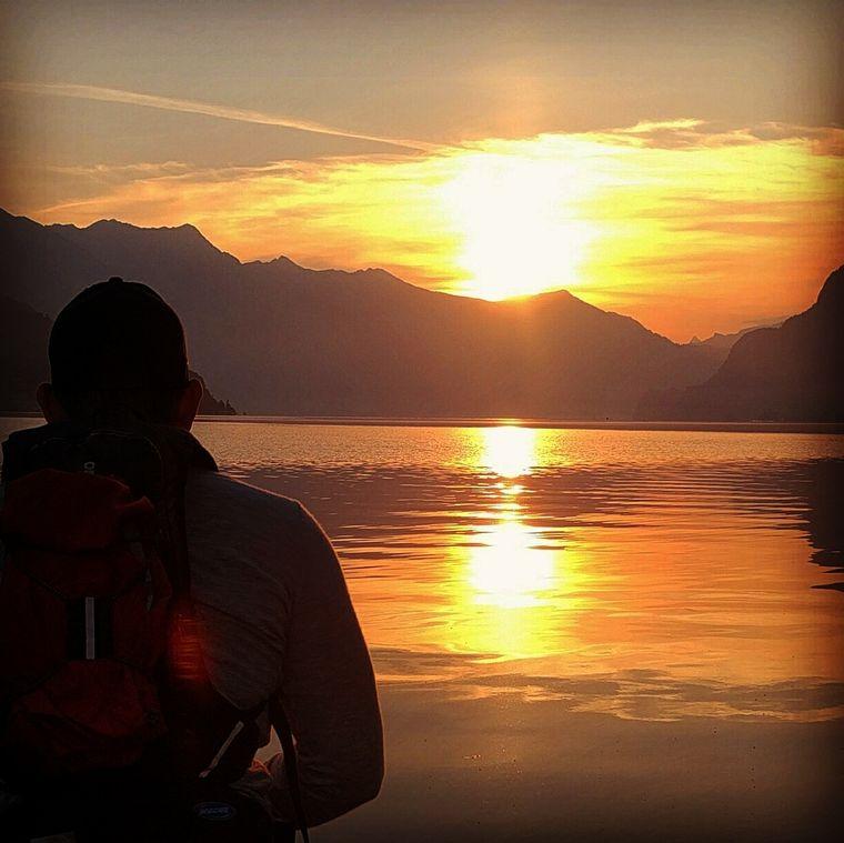 Eamon schaut in den Sonnenuntergang an einem See.