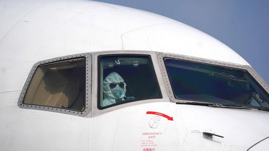 Ein Pilot mit Atemschutzmaske sitzt im Cockpit bei einem Flug nach Wuhan.
