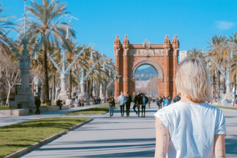 Eine Frau steht vor dem Arc de Triomf in Barcelona.