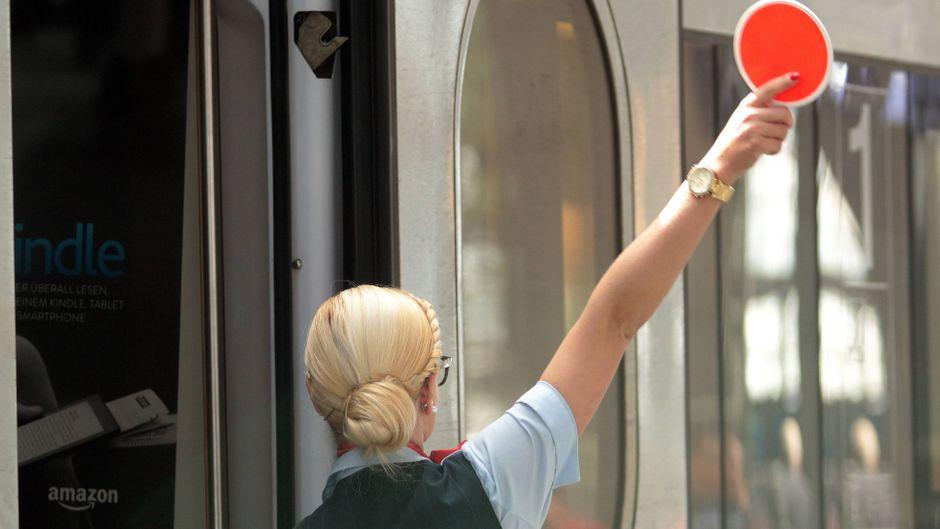 Zugbegleiterin der Deutschen Bahn fertigt einen ICE im Hauptbahnhof Frankfurt, Deutschland, ab.