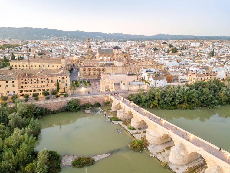 Drohnenaufnahme der berühmten römischen Brücke und der Mezquita-Catedral de Córdoba in Andalusien.