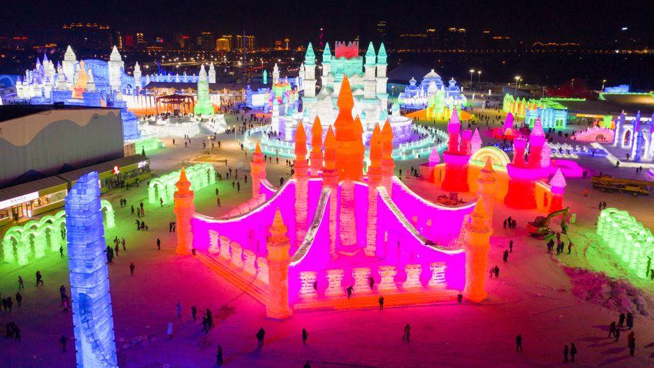 Bunt beleuchtete Paläste aus Schnee und Eis auf dem Harbin International Ice and Snow Sculpture Festival in China.