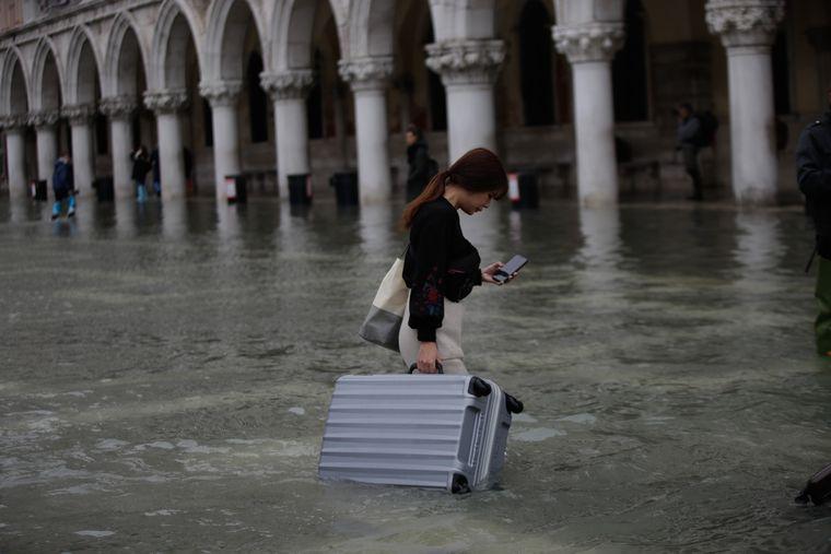 Touristin auf dem überfluteten Markusplatz in Venedig.