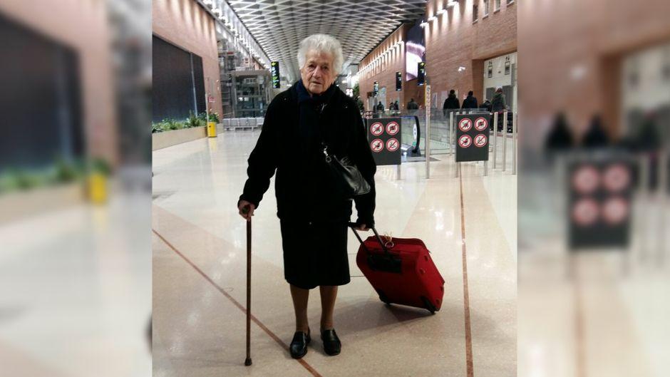 Oma Irma (93) am Flughafen in Italien. Sie reist nach Kenia, um dort Waisenkindern zu helfen.