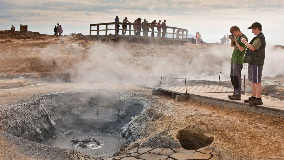 Touristen fotografieren Thermalquelle am Pass Námaskarð auf Island.