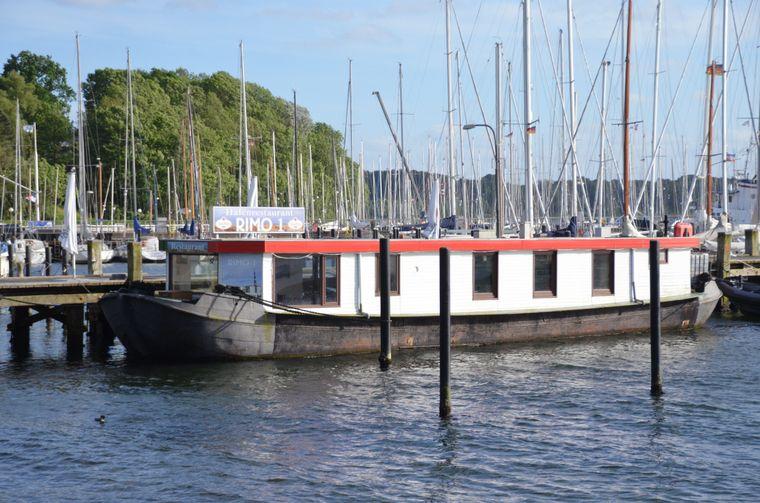 Rimo 1 ist ein umgebautes Schubboot, das mitten  im Hafen von Möltenort liegt.