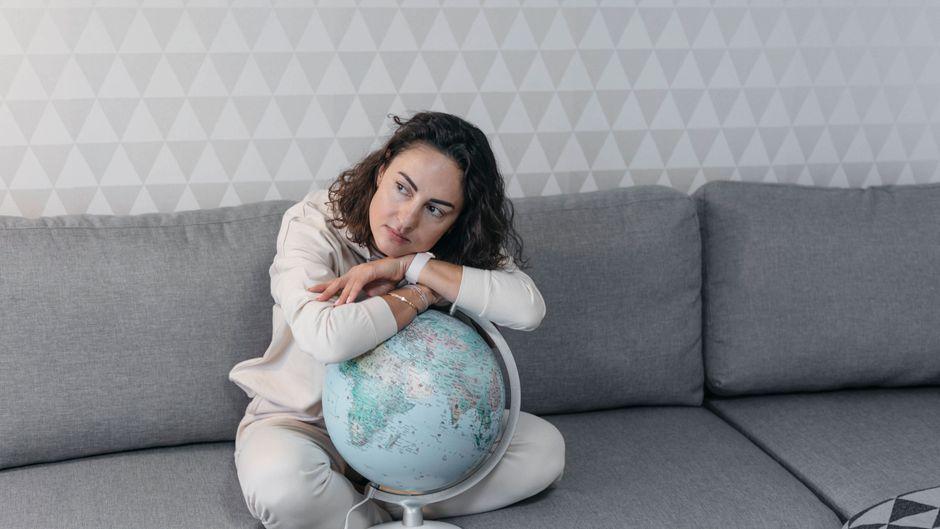 Frau sitzt mit Globus auf dem Sofa. (Symbolbild)