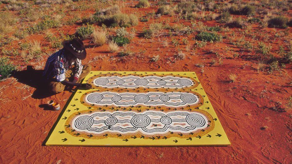 Ein Aborigine malt im Outback von Australien