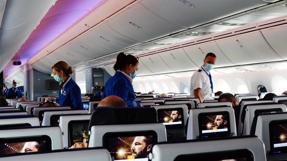 Flugbegleitende gehen in einer Flugzeugkabine durch die Sitzreihen. Wie macht man sich einen Flug auf dem Mittelplatz erträglicher?