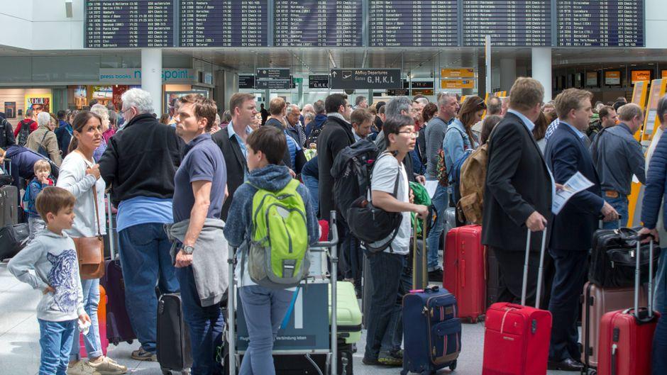 Passagiere warten an den Schaltern im Flughafen München.