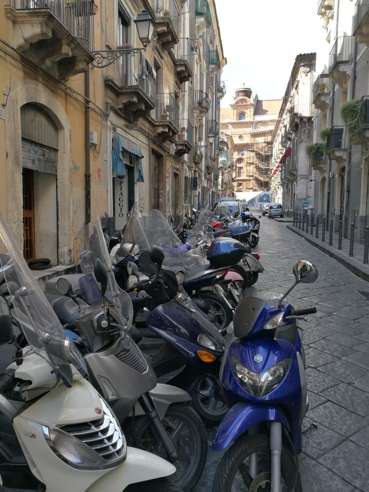 Typische Straße in Catania: Etwas verlebt und viele Vespas am Rand.