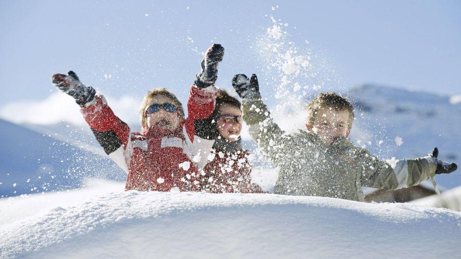 Kinder toben im Schnee im Winter