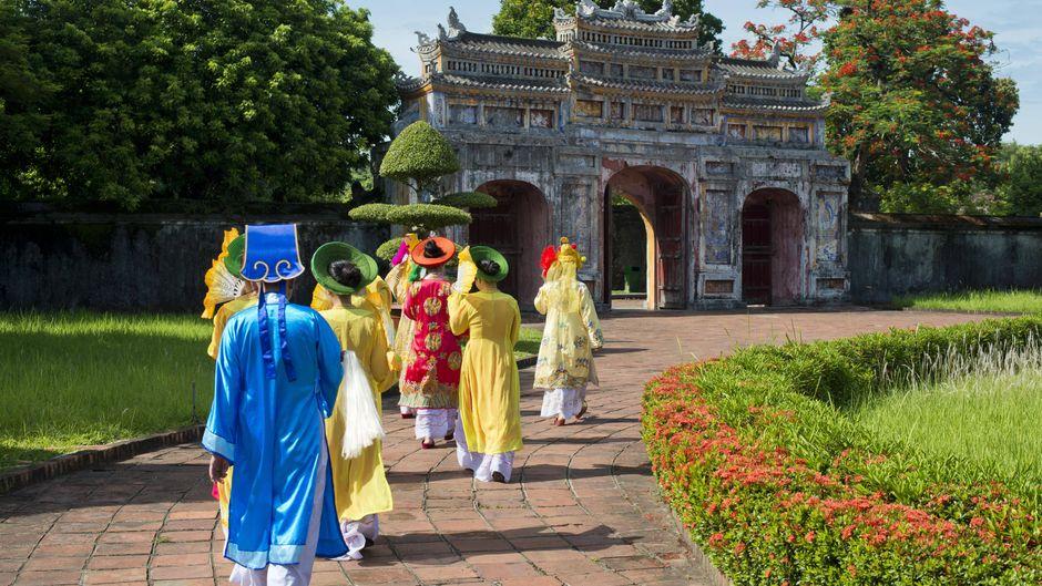 Vietnamesische Komparsen in traditionellen Gewändern laufen durch Westtor, Chuong Duc, Kaiserpalast Hoang Thanh.
