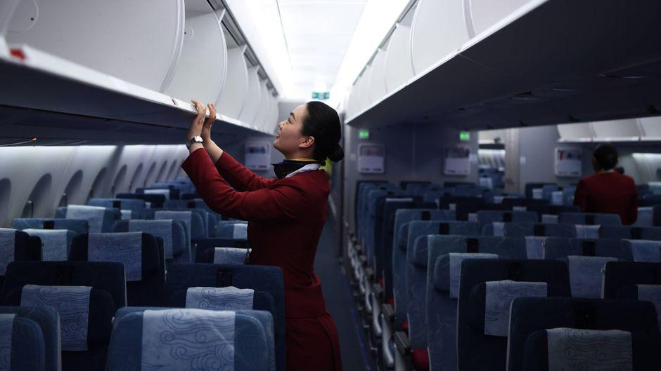 Eine Stewardess im leeren Flugzeug.