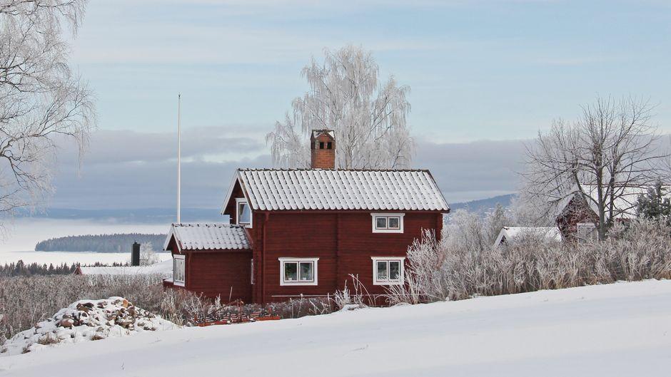 Ein rotes Holzhaus in verschneiter Landschaft in Dalarna in Schweden.