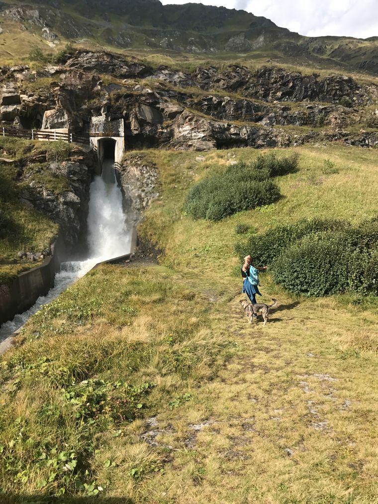 Anina Grosser und Hund an einem Wasserfall in den Alpen.